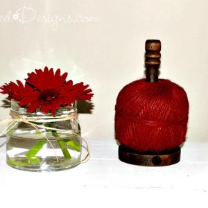 red gerber daisies and wood spool with red twine