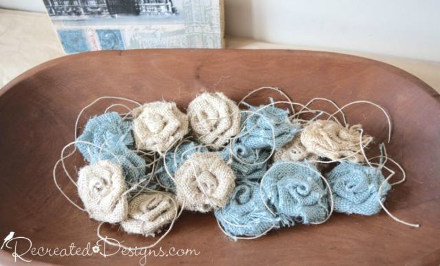 Blue and beige burlap flowers in a wooden bread bowl