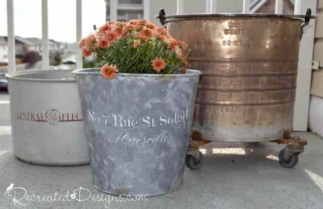 a collection of metal pails that will be used for flowers