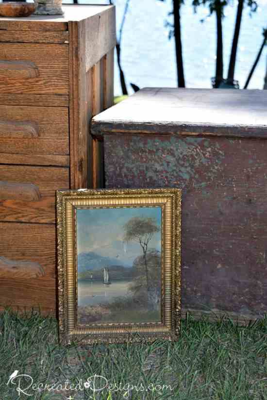an oil painting sitting against an antique trunk and some oak drawers