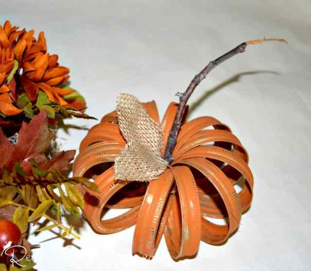 pumpkin made out of mason jar rings painted orange, twig and burlap leaves