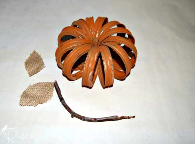 mason jar rings painted orange being made into a pumpkin with a stick for a stem and burlap leaves