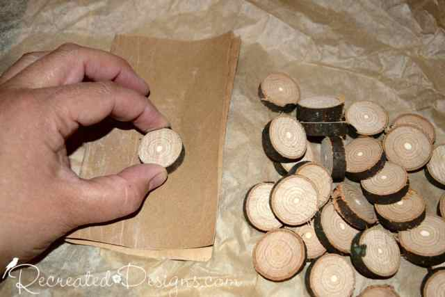 sanding small wood slices that will be used as checkers