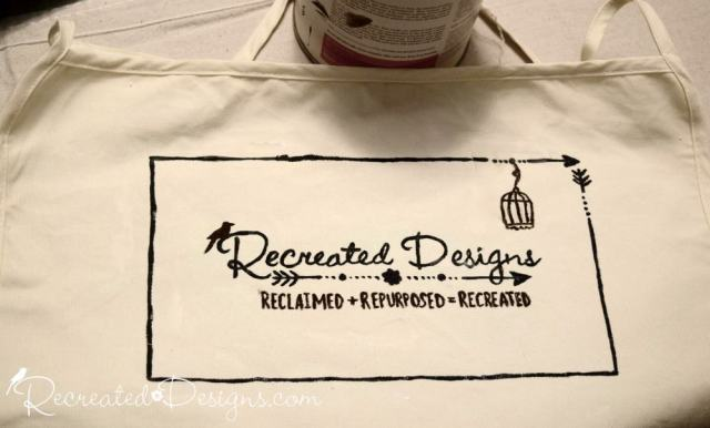 hand-painting an apron with a logo