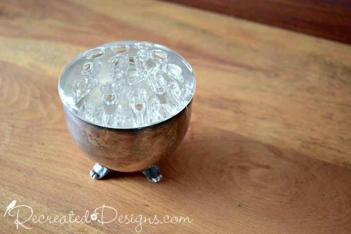 glass flower frog in a silver cup