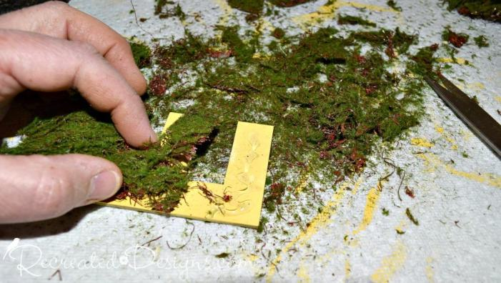 gluing moss onto yellow painted letters