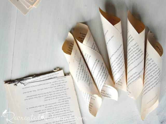 several cones out of old book pages ready to make into a paper flower