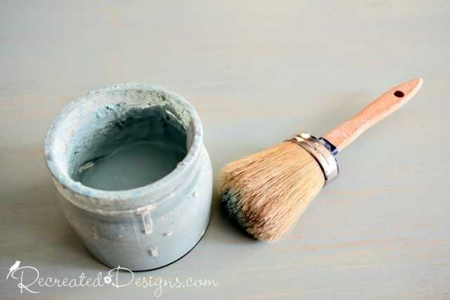 a glass jar filled with paint and a paint brush