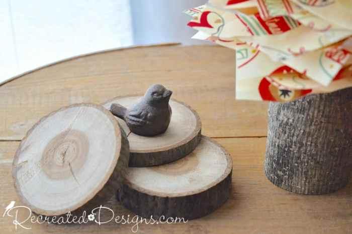 small wrought iron bird on wood slices