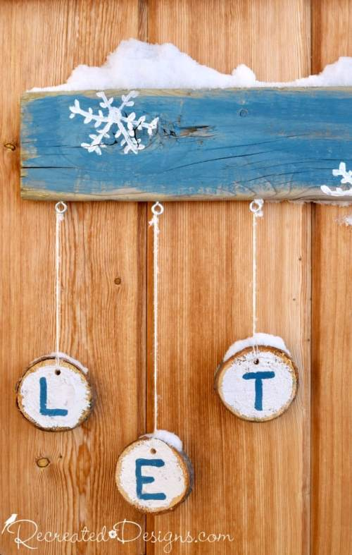 wood slices hanging from an outdoor Let it Snow sign