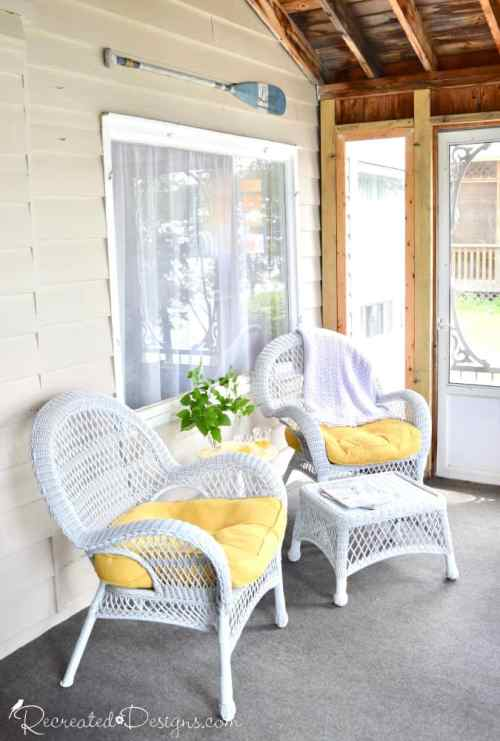 cottage porch with comfy chairs and bright yellow pillows