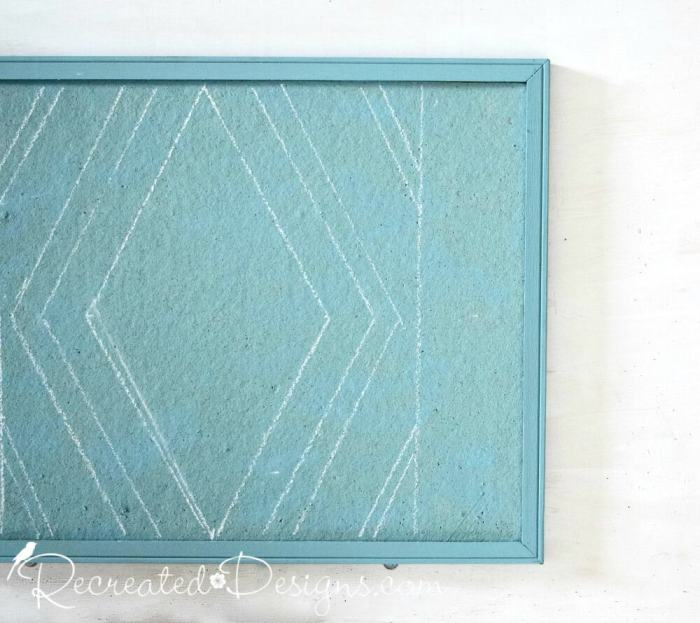 using chalk to draw a pattern on a painted cork board