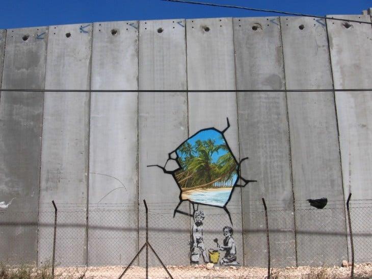 Grafiti de Bansky que muestra un hoyo en la pared que muestra una playa