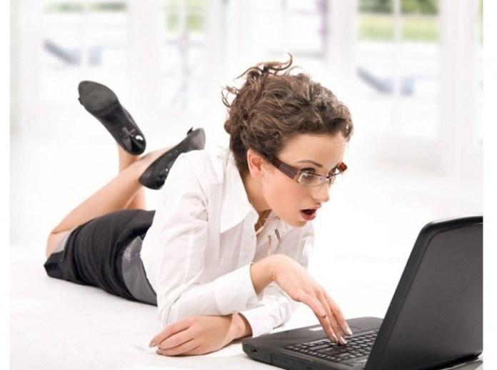 mujer que esta sorprendida al ver algo en la computatdora