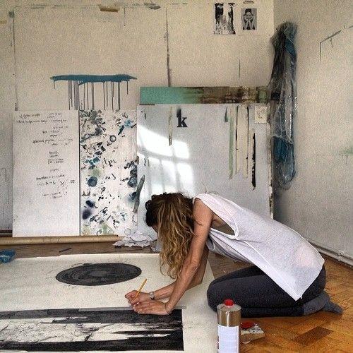 mujer hincada pintando un cuadro en el suelo