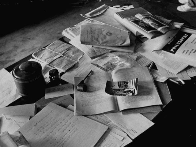 escritorio con libros abiertos regados por toda la mesa