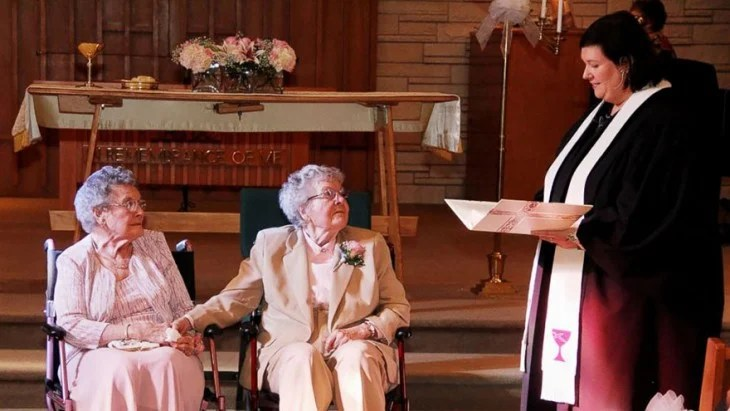 mujeres ancianas en sillas de ruedas junto a un pastor que oficia su boda