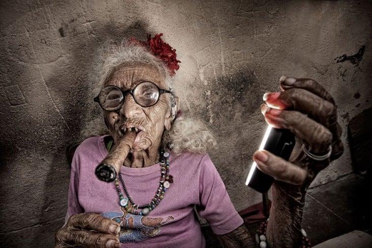 mujer anciana vestida de rosa fumando un puro mientras es fotografiada