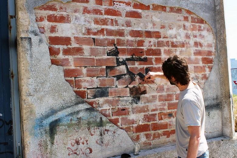 Pejac haciendo un dibujo en un muro en ladrillo