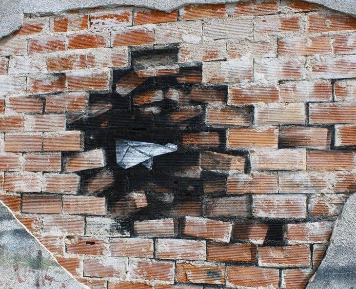 avioncito de papel en un muro de ladrillo