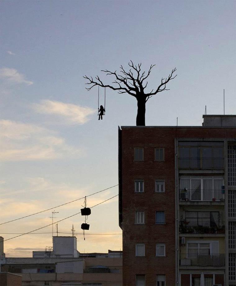 niña columpliando en un arbol arriba de un edificio