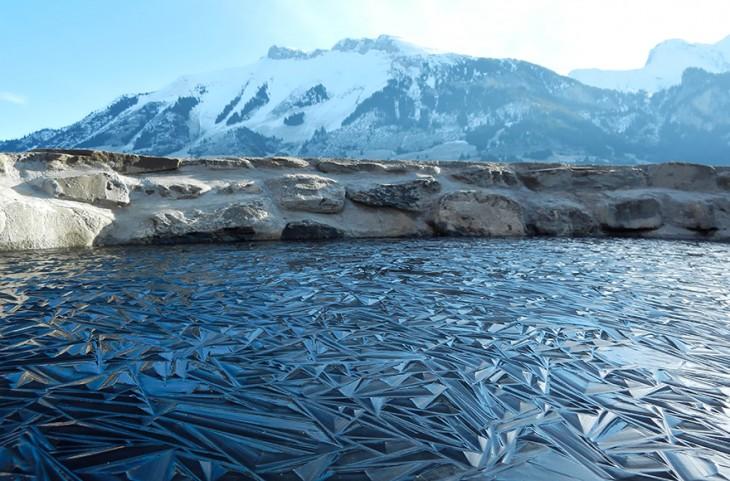Paisaje de una laguna congelada en Suiza con montañas a lo lejos