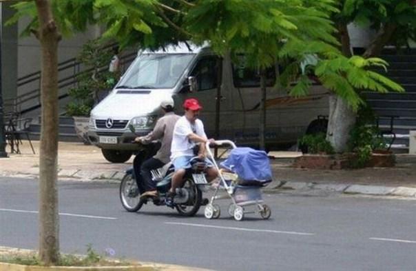 papá en motoneta con la carreola de su bebé