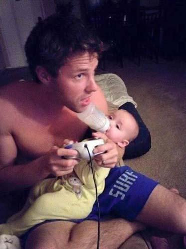 papá le da biberón a su hijo mientras juega videojuegos