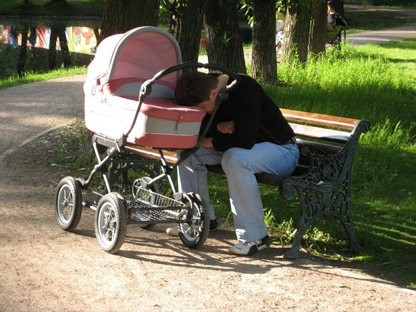 papá se duerme en el parque mientras su bebé está en la carreola