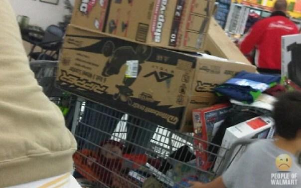 bebé dormido en carrito de compras con cajas encima