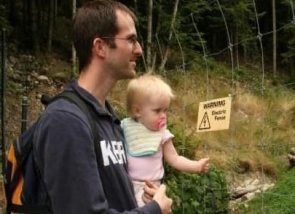 bebé agarra la cerca eléctrica mientras está en los brazos de papá