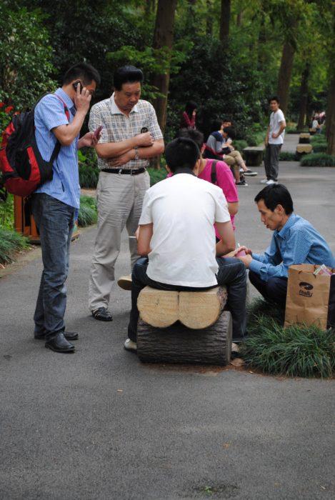 Hombre sentado sobre un tronco de madera cortado pero da la impresión de que es su trasero