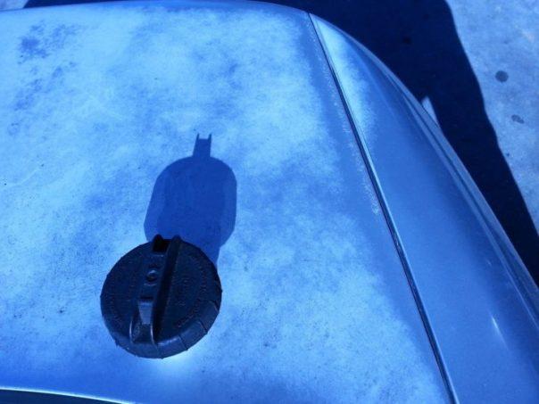 Fotografía de una tapa que con el reflejo del sol hace que aparezca una sombra de Batman