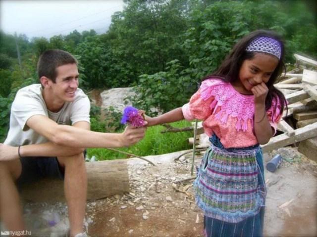 foto de turista que le otorga una flor a niña
