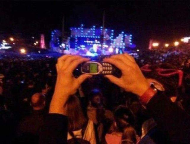 hombre manteniendo un celular viejo en un concierto