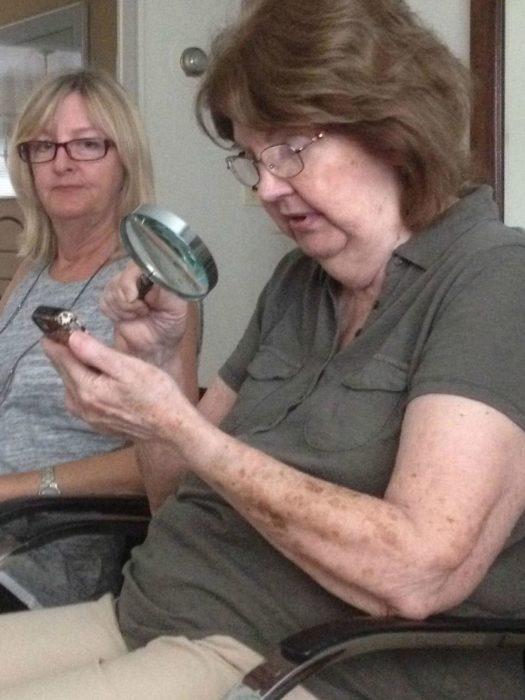 una señora mira a otra que está viendo el celular con una lupa