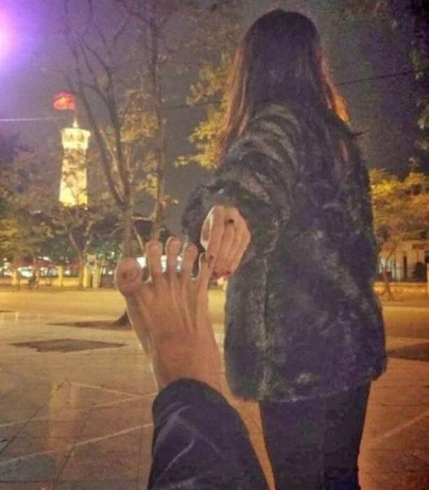 mujer jala los dedos de los pies de un hombre