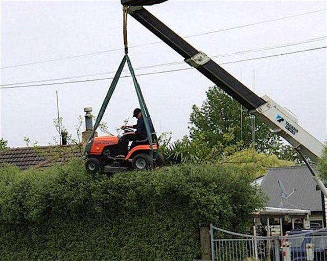 Hombre podando sostenido por una máquina