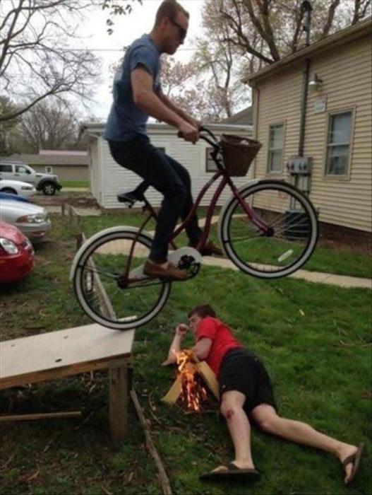 chico brincando en la bicicleta sobre otro amigo