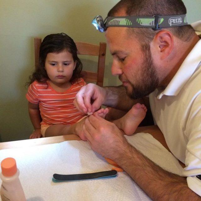 papá haciéndole pedicure a su hija