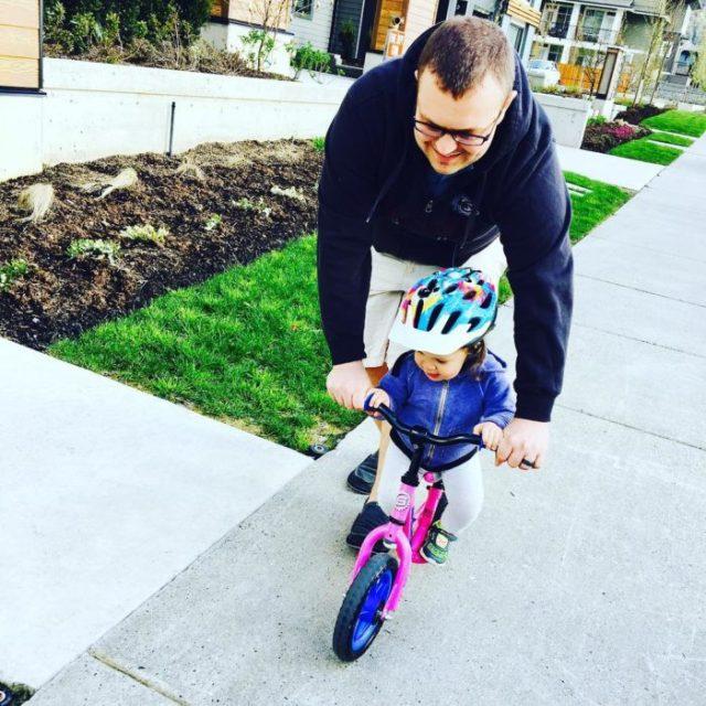 papá enseñando a su hija a caminar en bicicleta