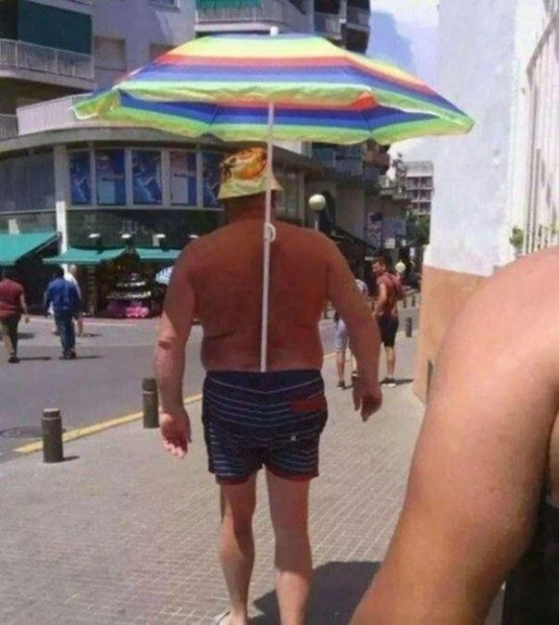 hombre con sombrilla dentro de su traje de baño