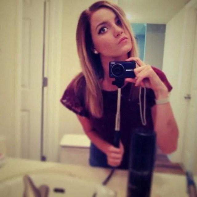 mujer utilizando un selfie stick con una cámara digital