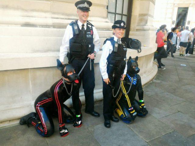 dos policias con correa atada a 2 humanos vestidos de perros