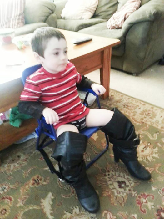 niño sentado utilizando botas de mujer
