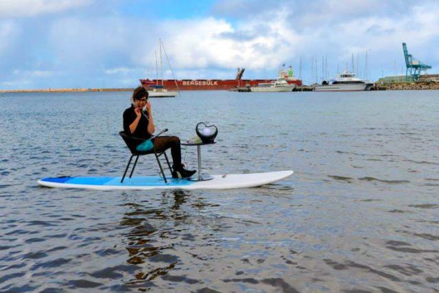 mujer replicando el teléfono en una tabla de surf