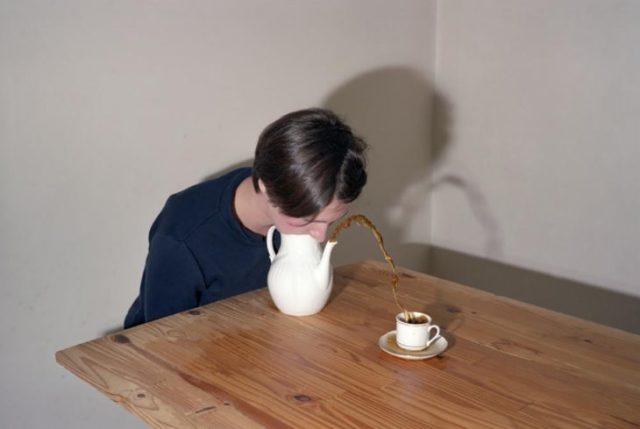 mujer sopla una tetera y el líquido cae en una taza
