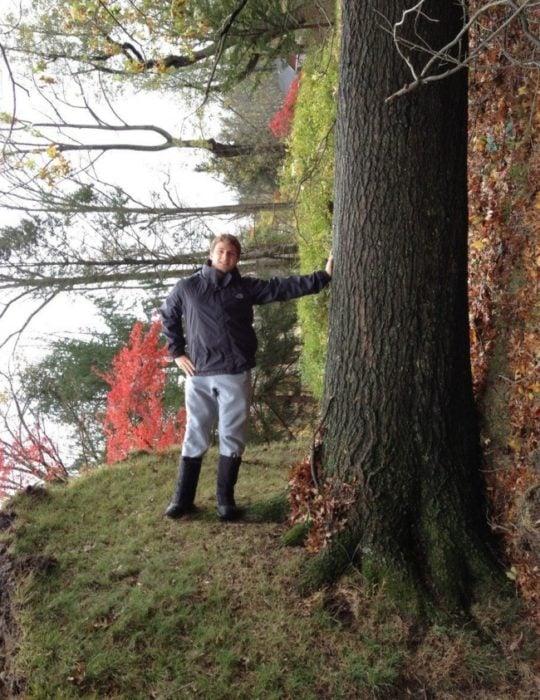 hombre recargado en un leño mas todo el bosque está acostado