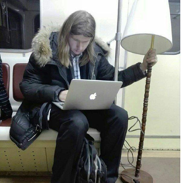hombre con una mac y una lámpara en el metro