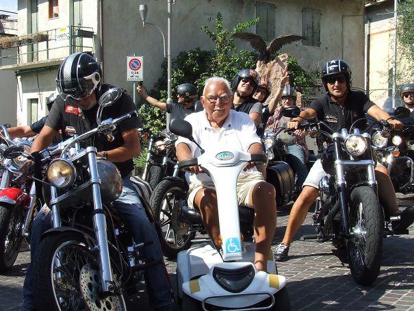 abuelo en silla eléctrica al lado de motociclistas
